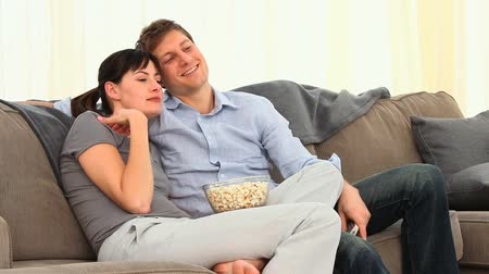 pihenő : Young couple watching tv on their sofa