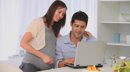 feminino : Future parents using a laptop in their kitchen