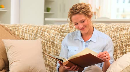 фото : Curly-haired woman looking at an album on her sofa