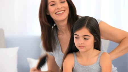 haj : Brunette mother fixing hair of her daughter in the living room