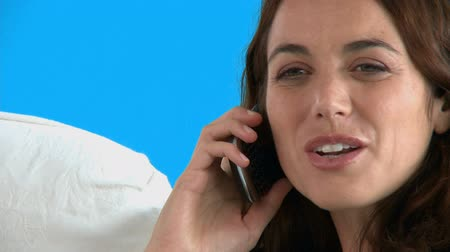 закрывать : Happy hispanic woman talking on phone on the sofa against a blue background