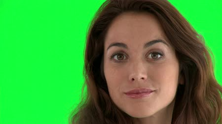 dış : Close-up of an attractive hispanic woman smiling at the camera against a green background Stok Video