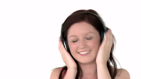 harmonia : Charming girl listening to music against a white background Wideo