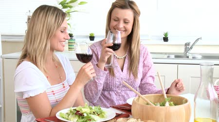 wine red : Attractive women drinking wine eating salad sitting in a kitchen Stock Footage