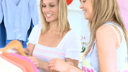 ubrania : Young cute women trying pullover in a clothes shop