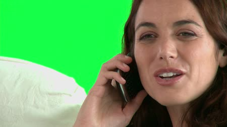испанец : Cheerful hispanic woman talking on phone on the sofa against a green background