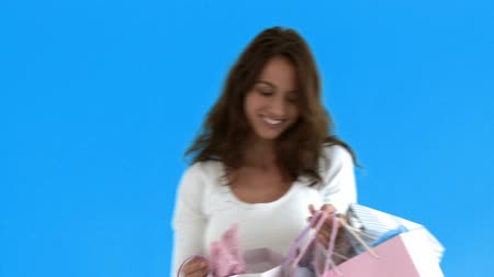 selecionar : Cheerful hispanic woman holding shopping bags against a blue background