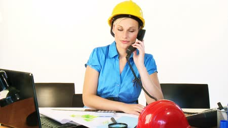 müteahhit : Blonde young architect woman talking on phone in office while she is working with construction plans