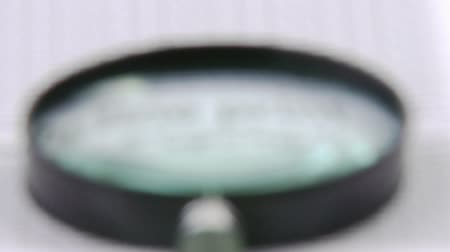 vizsgálat : Footage of a blurred magnifying glass getting sharp in high definition