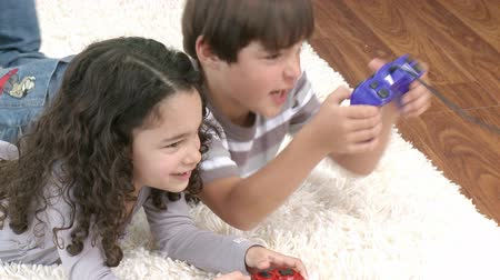 eğlence oyunları : Footage in high definition of happy children playing video games on the floor at home Stok Video