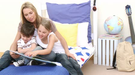 o : Mother reading a book with her children in bedroom. Concept of culture. Footage in high definition