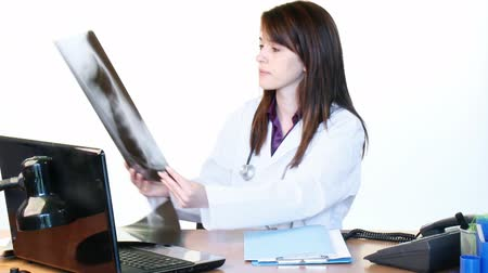 рентгенологическое : Brunette doctor examining an x-ray and using a laptop in her hospital office - High Definition Стоковые видеозаписи