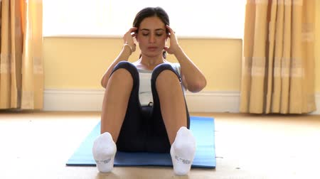gym : Positive woman doing sit-ups at home Stock Footage