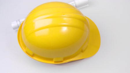 hard hat : Footage of a high view of a yellow hard hat and a plan turning in high definition