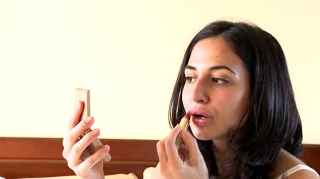 ruj : Portrait of a voluptuous woman putting lipstick at home