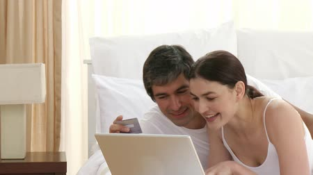 покупка товаров : Footage in high definition of smiling couple lying in bed shopping online with a laptop