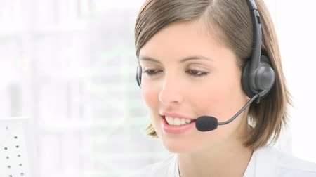 irodaház : Close-up of smiling woman working in a call center. Customer service. Footage in high definition