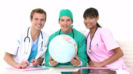 paramedic : International medical team holding a terrestrial globe against a white background