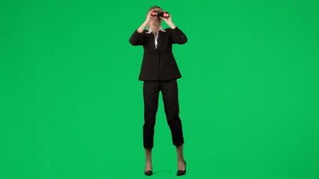 bulmak : Footage of a businesswoman looking through binoculars against green screen Stok Video