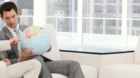 dava : Businessmen looking at a terrestrial globe sitting on a sofa