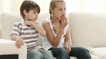 родной брат : Footage in high definition of little boy and girl on sofa eating and watching television