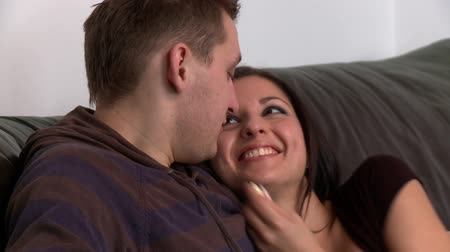 casal heterossexual : Portrait of a romantic couple embracing sitting on sofa at home