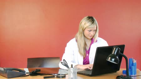 lékař : Beautiful female doctor using a laptop in hospital office and smiling at the camera footage in High Definition