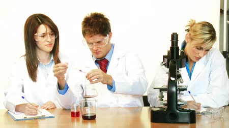laboratorní plášť : Young scientists working in a laboratory with microscope and test-tube and supervisor checking their work