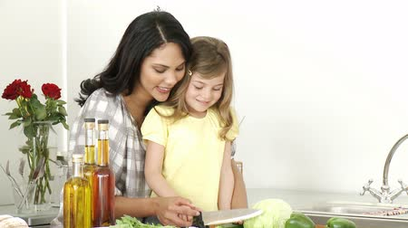 prepare food : Footage in high definition of a mother and a little girl cutting vegetables in the kitchen
