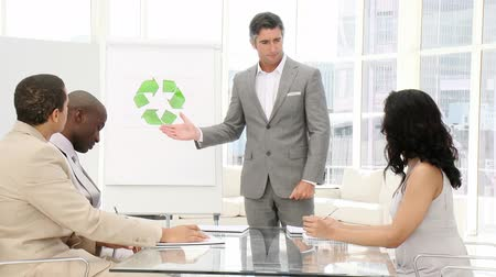 fejlesztés : Confident businessman presenting recycling sign in the office