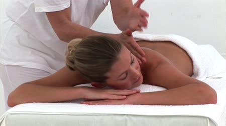 терапия : Quiet woman enjoying a back massage in a spa center
