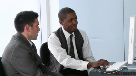 executivo : Footage of an Afro-American businessman using a computer in office with his colleague in high definition