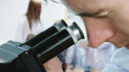 устройство : Man looking into a microscope