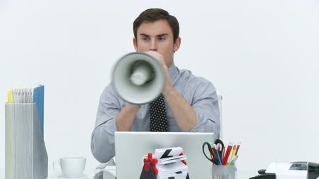 megafon : Businessman sitting in office shouting through a megaphone to his team. Footage in high definition