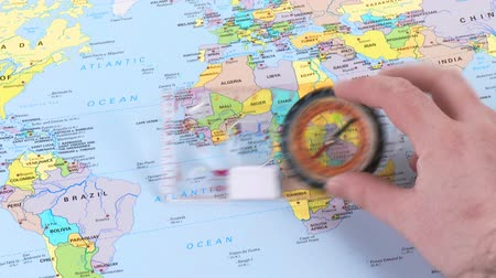 north america : Footage of a hand moving a compass over a world map in high definition