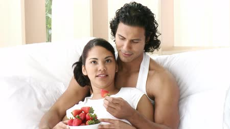 sitting room : Happy couple sitting in bed eating strawberries. Footage in high definition