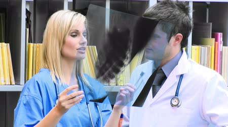 консалтинг : Young female and male doctors examining an x-ray in hospital footage in high definition Стоковые видеозаписи