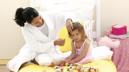matka dziecko : Mother playing with her daughters toy cubes on the bed. Footage in high definition. Concept of education
