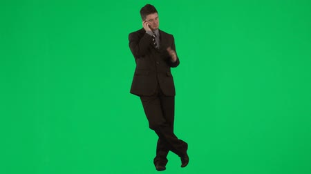 стоять : Attractive businessman talking on mobile phone against green screen footage
