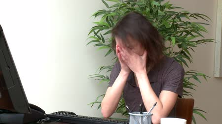 disinterest : Depressed woman working at a computer at home Stock Footage