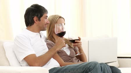 buys : Man and woman using a laptop and drinking wine on sofa at home. Pleasure and computer concepts. Footage in high definition