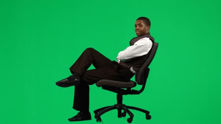 стулья : footage of an Afro-American businessman relaxing on a business chair against green screen Стоковые видеозаписи
