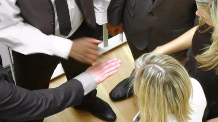 стоять : Close-up of international business team with hands together and blonde businesswoman smiling at the camera footage