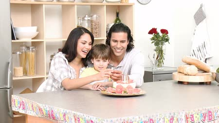 a party : Little boy celebrating his birthday with his parents at home. Footage in high definition Stock Footage