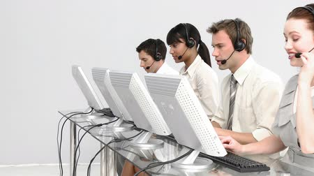 kontakt : Concentrated people working in a call centre against a white background