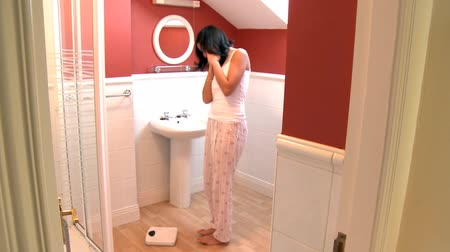 estilo de vida saudável : Blissful woman checking her weight in the bathroom