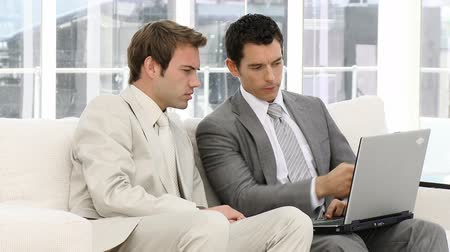 suit and tie : Serious businessmen using a laptop sitting on a sofa Stock Footage