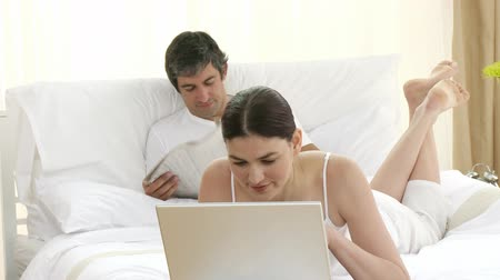 мебель : Footage in high definition of attractive woman using a laptop and man reading a newspaper in bed Стоковые видеозаписи
