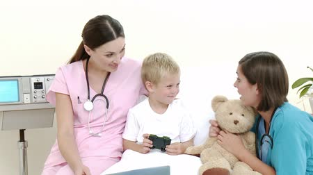 maci : Little patient talking to a nurse and a pediatrician while he is recovering in hospital. Footage in high definition. Concept of healthcare Stock mozgókép