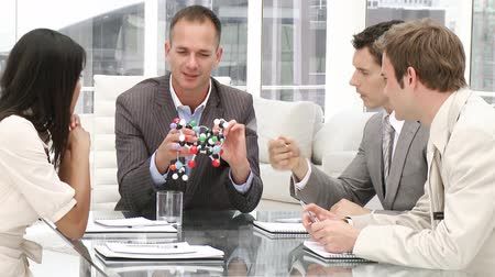 ortam : Confident manager holding a molecule in a meeting with his team